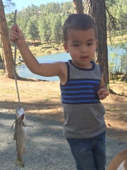 Two-year-old Jase Barttram shows off the fish he caught at Alto Lake.