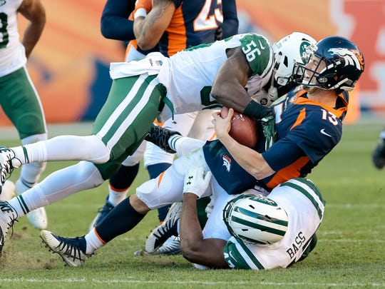 New York Jets outside linebacker David Bass (47) and inside linebacker Demario Davis (56) in the second quarter at Sports Authority Field at Mile High.