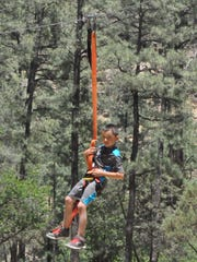 A young boy takes a ride down the news zipline at the
