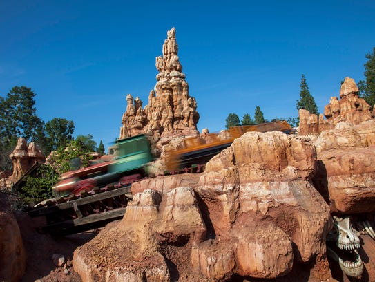 A train zips through Big Thunder Mountain and past