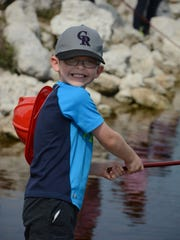 """Steven Fieber, 5, fishes with a cane pole at the Collier County Junior Deputies League's tenth annual """"Kids Love Fishing"""" event."""