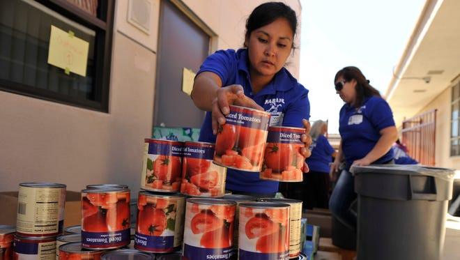 Volunteer Laura Ibara stacks canned tomatoes as she get ready to distribute food at Naranca Elementary School in El Cajon, Calif.