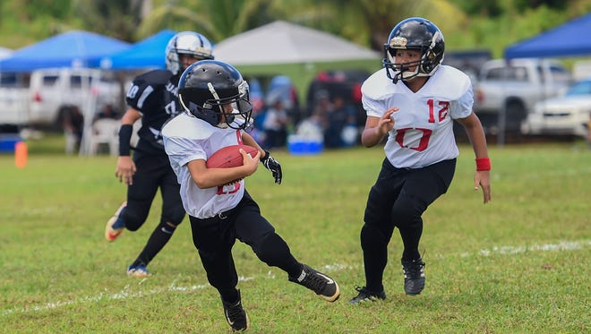 Outlaws player Christopher Angoco avoids Guam Raiders defenders during their Guam National Youth Football Federation game at Eagles Field on Aug. 12, 2017.