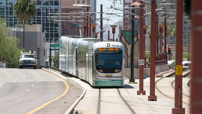 A light-rail train arrives at a stop in downtown Phoenix on Monday, Aug. 3, 2015.