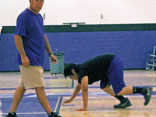 Mescalero Apache School head football coach Leonard Velasquez conducts conditioning workout Tuesday afternoon in the MAS gymnasium.