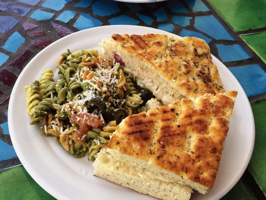 The chicken panini (7.99) is made with fresh baked focaccia bread, chicken salad, and a flavorful cheese spread with a choice of side salad, pesto pasta salad, or chips and salsa.
