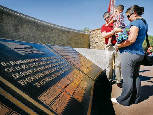Calvin Barreras looks at the Field of Honor Memorial at Fort Bliss where his father Command Sgt. Maj. Martin Barreras' name was added. Barreras was shot in Afghanistan on May, 6, 2014, and later died at a San Antonio hospital. Barreras played a crucial role in the rescue of Jessica Lynch, a member of the 507th Maintenance Company, in 2003. Calvin was joined at the memorial by his wife Melissa Barreras and son Noah, 2.