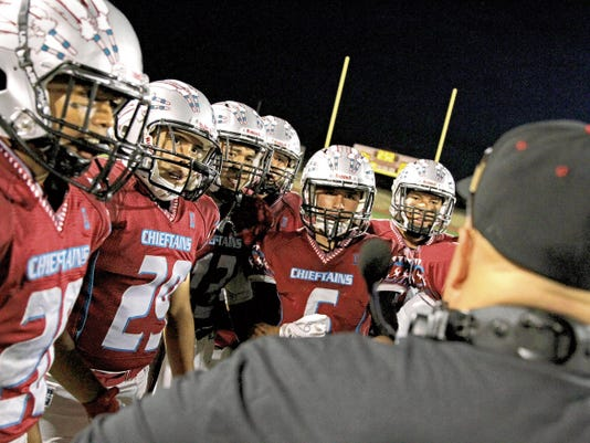 Shiprock players listen to their coaches during a timeout in last week's game against Socorro at Chieftain Stadium in Shiprock.