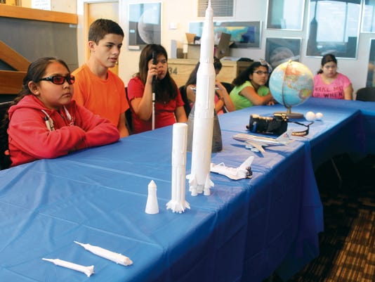 New Mexico School for the Blind and Visually Impaired campers listen to a lecture at the New Mexico Museum of Space History Thursday morning. Campers got to touch and feel small scale models of spacecraft replicas to help them visualize them better.