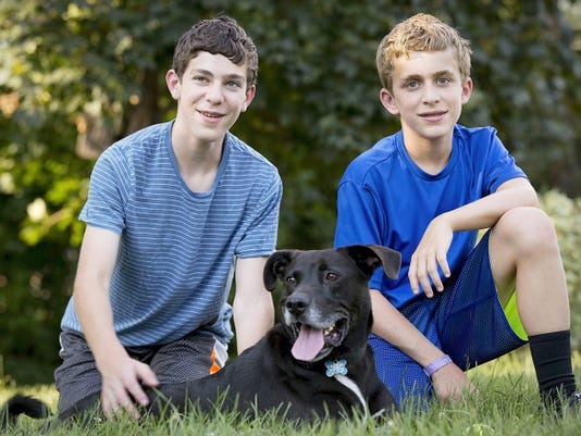 Jacob Rubin, 14, left, and his brother Jonathan, 12, are pictured with their dog Bailey at their home in Long Grove, Illinois. The brothers signed up Bailey D. Dog as an independent candidate for president.