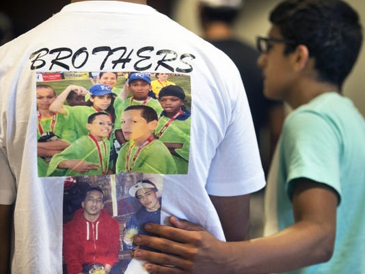 A mourner pauses by a t-shirt made for remembrance in this June 22 photograph from the funeral of Angel Berrios, Jr., 21 and his younger brother Abdiel Vazquez-Soto, 19.
