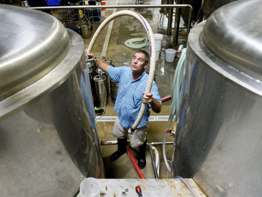 Gunpowder Falls Brewing owner Martin Virga lifts up a hose for a tank on Wednesday at the brewery in Shrewsbury Township. Virga brews traditional German lagers, and targets his distribution to strong markets in locations such as Baltimore, Maryland and Washington, D.C.