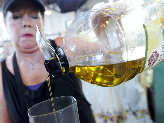 Cheryl Ness, co-owner of Saucy Girls, pours olive oil into a mixer while making hummus at her stand at Central Market on Thursday.