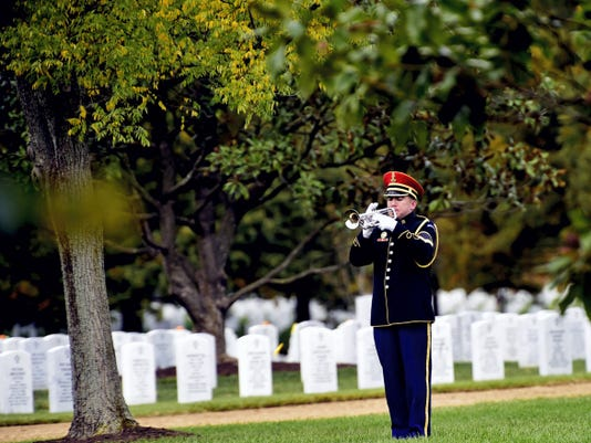 """Army Staff Sgt. Kevin Gebo, U.S. Army Band """"Pershing's Own,"""" plays taps during a funeral service for Cpl. Robert Meyers, Monday at Arlington National Cemetery. Meyers was killed during the Korean War and his remains were recently identified."""