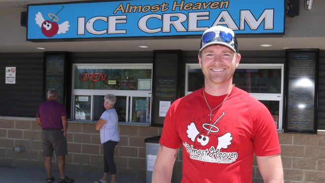 Jared Truax, chief financial scooper, is shown outside Almost Heaven Homemade Ice Cream in Plain Township. A second store is under construction in Alliance.