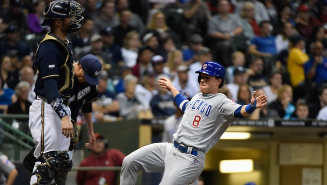 Chicago Cubs left fielder Chris Coghlan (8) scores in front of Milwaukee Brewers catcher Jonathan Lucroy (20) in the seventh inning at Miller Park.