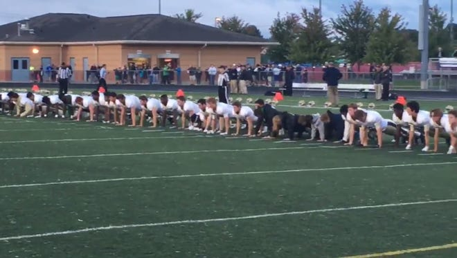 Members of Cathedral and FIshers' football teams did 22 push-ups prior to Friday night's game to raise awareness for military veteran suicide.