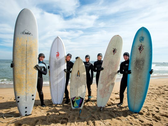 Jen Cox, Michelle Sommers, Laurel Harrington, Lora Cole and Sarah Schwind stand with their surfboards before a winter surfing session in Ocean City.