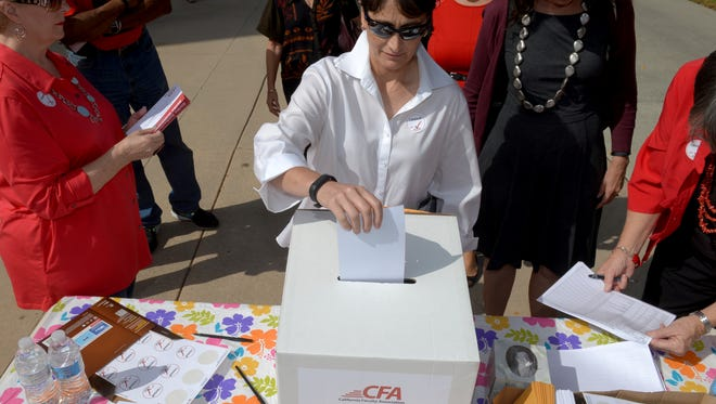 Cal State University professor Sherry Span drops her ballot in the box as Cal State University faculty hold a strike vote, with professors holding rallies at CSULB campus in Long Beach Calif., Monday Oct. 19, 2015. Faculty members at the California State University's 23 campuses are voting online and in person starting Monday on whether to permit their labor union to call a strike over stalled salary negotiations.  (Thomas Cordova/the Daily Breezevia AP)