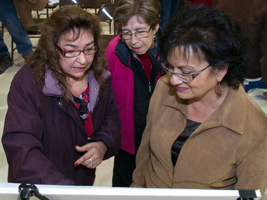 Vado residents Dora Dorado, left, and Mayo Ceniceros, center, discuss the map of the proposed multipurpose motor sports complex with Dona Ana County employee Marty Olivas at a community meeting at the Del Cerro Community Center in Vado on Thursday, Jan. 19, 2017.