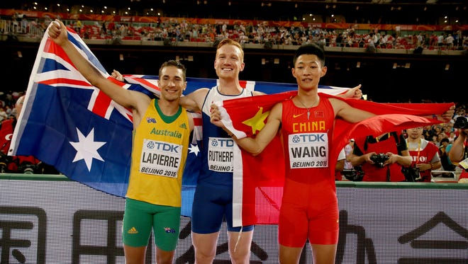 Greg Rutherford, center, and Fabrice Lapierre, right, who train in Phoenix won gold and silver in long jump at the World Track Championships.