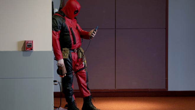"""Chris Simons """"Deadpool"""" chargers his phone while at Flower City Comic Con at the Rochester Riverside Convention Center on Saturday, April 23, 2016. The convention continues Sunday."""
