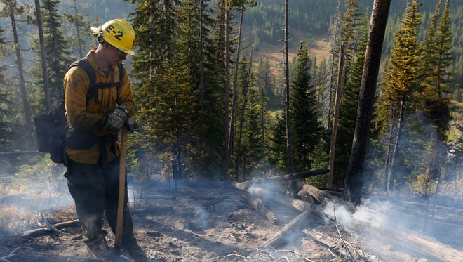 Firefighter Austin Edwards, of California's Whiskeytown National Recreation Area Fire Module, stands in the smoking burn area of the Berry Fire during a mop up near the road to Yellowstone in Grand Teton National Park, Wyo., Saturday, Aug 27, 2016. (AP Photo/Brennan Linsley)