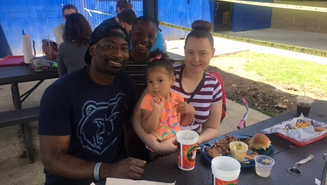 Steven and Carrie Tuggle with their daughter, 2, and nine-year-old son. Carrie brought the kids to Central BBQ for lunch on the patio, a spot that is much cooler than her downtown home, which lost power at 10:50 p.m. Saturday.