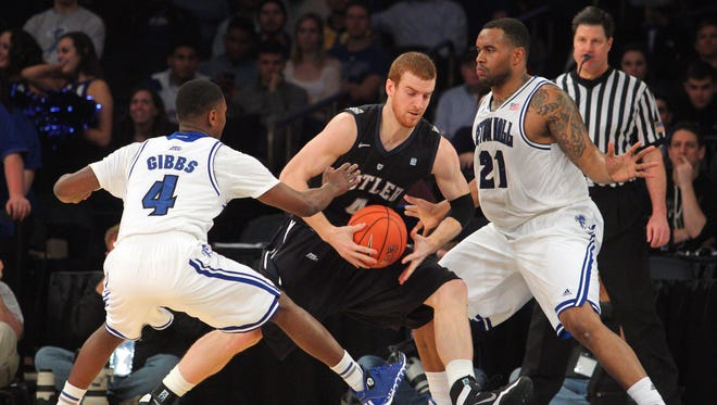 Butler Bulldogs forward Erik Fromm (4) dribbles the ball between Seton Hall Pirates guard Sterling Gibbs (4) and Pirates center Gene Teague (21) during the first half in the first round of the Big East tournament.