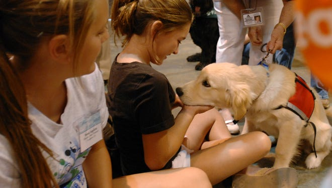 In this file photo, Sherlock, a Pets for Health therapy dog, visits kids at the Cajundome in 2009.  Pets for Health is planning to visit the Deaf Action Center's Cajun Campers Wednesday with therapy dogs.