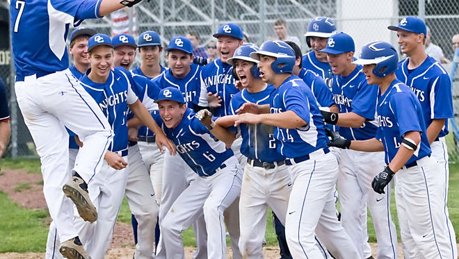 Members of the Oak Creek baseball team prepare to celebrate as Doran Turchin jumps onto home plate after breaking a 2-2 tie with a grand slam home run in the seventh inning of the Knights' 6-2 Greater Metro Conference win over host Franklin Thursday, June 19, 2014.