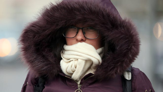 College student Cindy Nevarez bundled up for Tuesday's cold temperatures while walking along North Mesa Street near Interstate 10 in Downtown El Paso Tuesday.