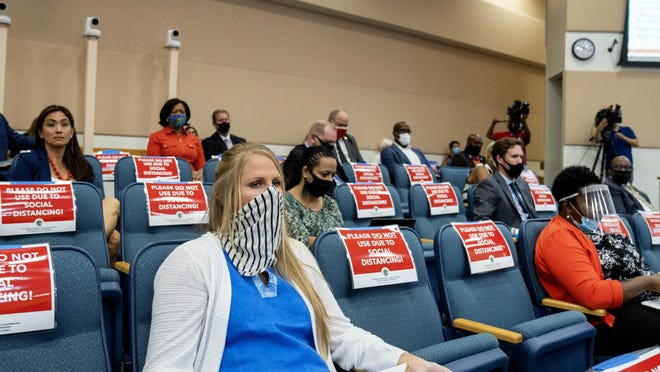 People practice social distancing while listening to Palm Beach County Health Director Dr. Alina Alonso give a presentation to county commissioners about COVID-19 in West Palm Beach Tuesday.