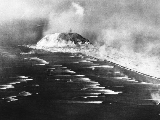U.S. Marines go ashore on Iwo Jima as explosions rock the coast.