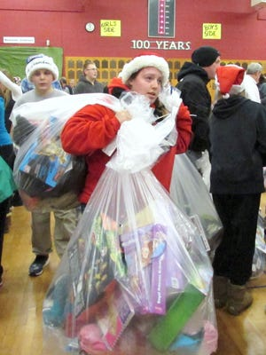 Volunteers load up with gift bags for needy families Christmas morning at Arctic League headquarters in Elmira.