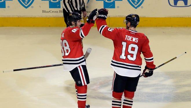 Chicago Blackhawks' Patrick Kane, left, celebrates with Jonathan Toews after scoring a goal against Boston Bruins during the shootout of an NHL hockey game in Chicago, Sunday, Jan. 19, 2014.  The Blackhawks won 3-2. (AP Photo/Nam Y. Huh)