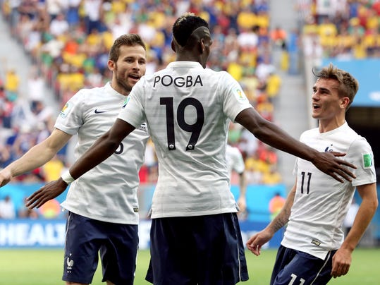 France's Paul Pogba (19) celebrates with teammates Yohan Cabaye, left, and Antoine Griezmann, right, after scoring his side's opening goal during the World Cup round of 16 soccer match between France and Nigeria at the Estadio Nacional in Brasilia, Brazil, Monday, June 30, 2014.  (AP Photo/David Vincent)