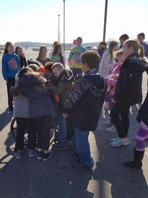 Students at Dodgeland Elementary School in Juneau crowd around Dennis Schulze, who is traveling by wheelchair from Janesville to Lambeau Field. He traveled past their school on Friday.