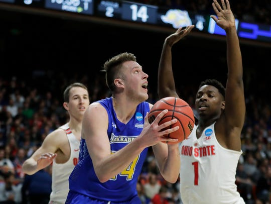 South Dakota State forward Mike Daum, left, puts up