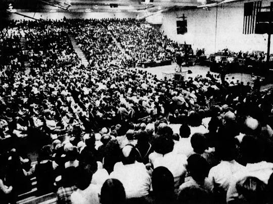 A crowd of 7,500 people listen as the Rev. Billy Graham preaches at Patrick Gymnasium at the University of Vermont in Burlington on April 23, 1982.