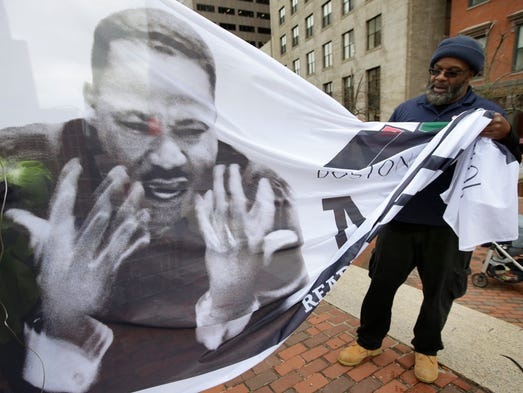 Steve Coachman, of Boston, right, unfurls a flag featuring