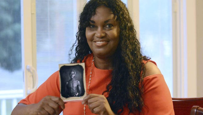 In this July 17, 2018, photo, Tamara Lanier holds an 1850 photograph of Renty, a South Carolina slave who Lanier said is her family's patriarch, at her home in Norwich, Conn.