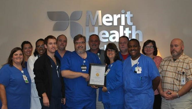 Merit Health Wesley Stroke Certification Committee poses with their certificate acknowledging Merit Health Wesley as an Advanced Primary Stroke Center.