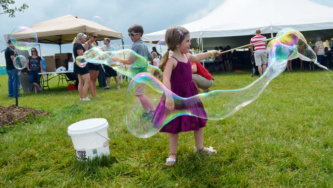 Matilda Johnsen, 4, and brother Hayden, 7, make bubbles with a stick, looped string and bucket of soapy water Saturday at North Liberty Blues and BBQ in Centennial Park.