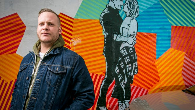 """Van Holmgren stands next to his mural for ABC's """"The Bachelor"""" on the side of RoCA. He had less than four hours to complete the artwork in early 2015."""