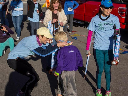 Dr. Catherine Kemmer, OB/GYN at Women's Medical Associates in Las Cruces and race organizer, awards a child during the 2015 Run with Your Doc event.