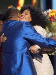 Anthony Anderson hugs Tracee Ellis Ross with the award