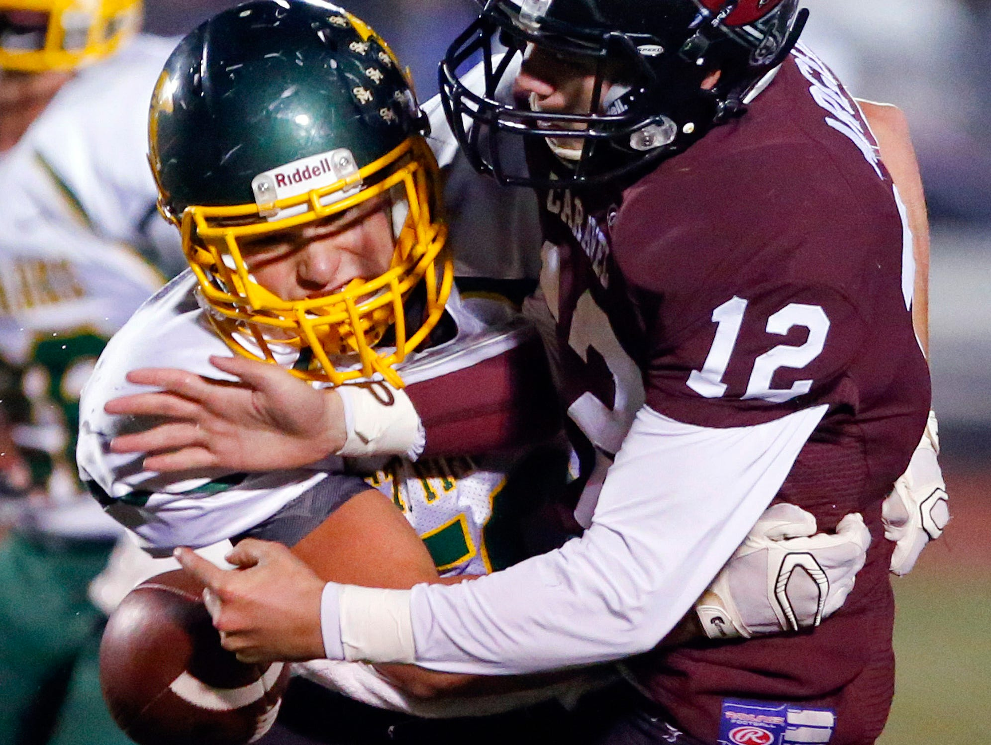St. Mark's Anthony McGonigle (left) breaks in on Caravel quarterback Jackson Argoe and forces a fumble in the first quarter at Caravel Academy Friday.