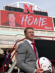 New Nebraska head NCAA college football coach Scott Frost poses at Memorial Stadium with a football helmet following a news conference in Lincoln, Neb., Sunday, Dec. 3, 2017. Frost is returning to Nebraska after orchestrating a stunning two-year turnaround at Central Florida. (AP Photo/Nati Harnik)
