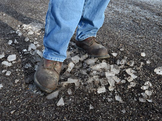 Chris Huett, Baxter County Road and Bridge superintendent, kicks up some ice on County Road 600 Tuesday morning.